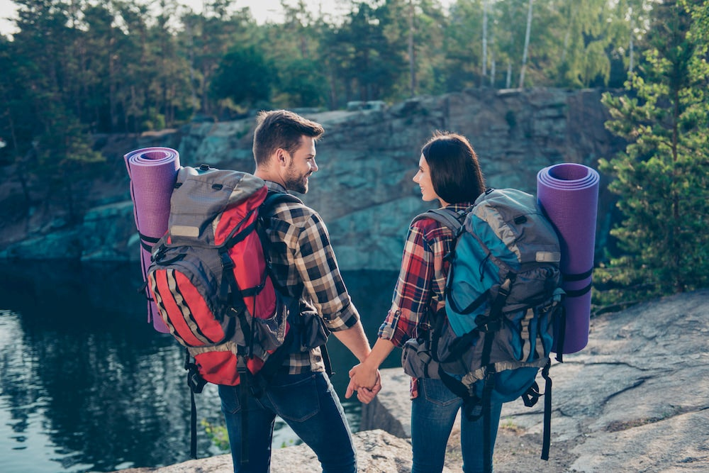 a couple on a backpacking trip wearing gear packs and romanticly holding hands in the wilderness