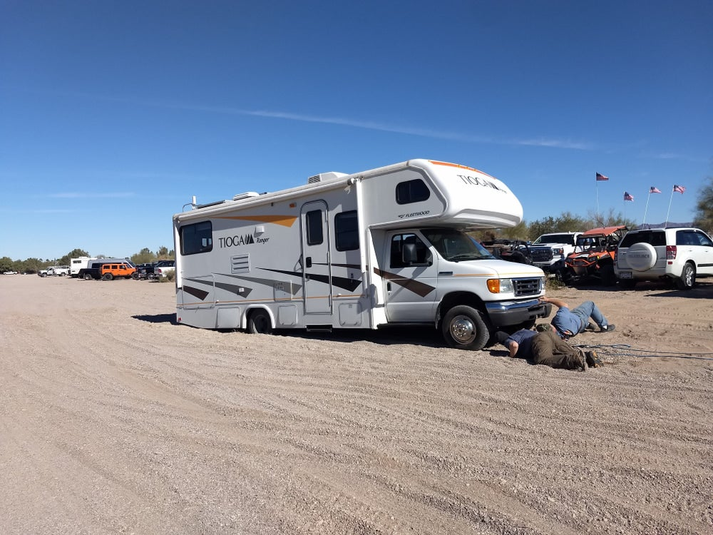 Men sprawled on ground in front of RV that is stuck in the sand.