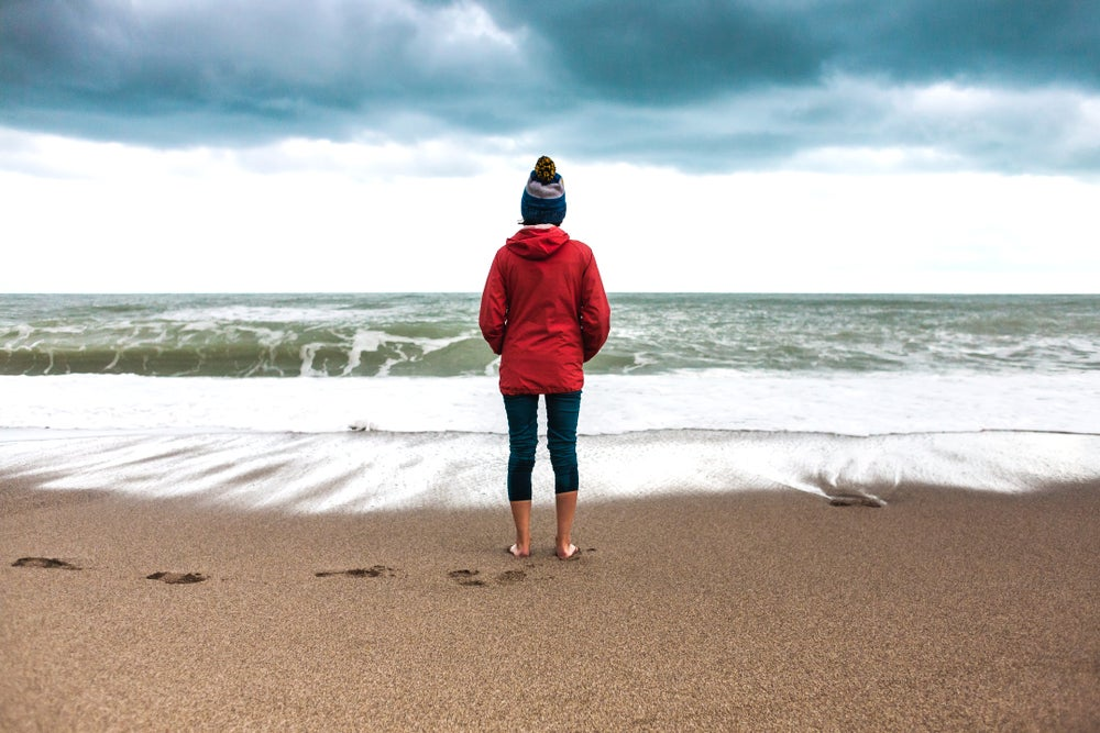 Woman standing in winter clothes while barefoot on the beach, facing the breaking tide.