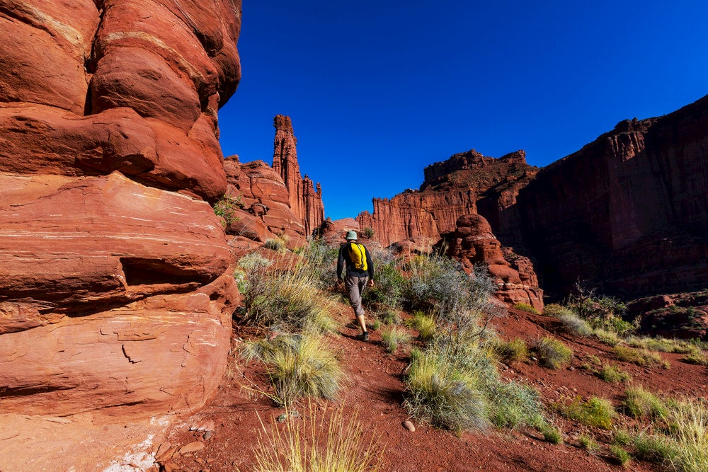 Man hiking among red rocks in moab, utah with Fisher Tower in the background