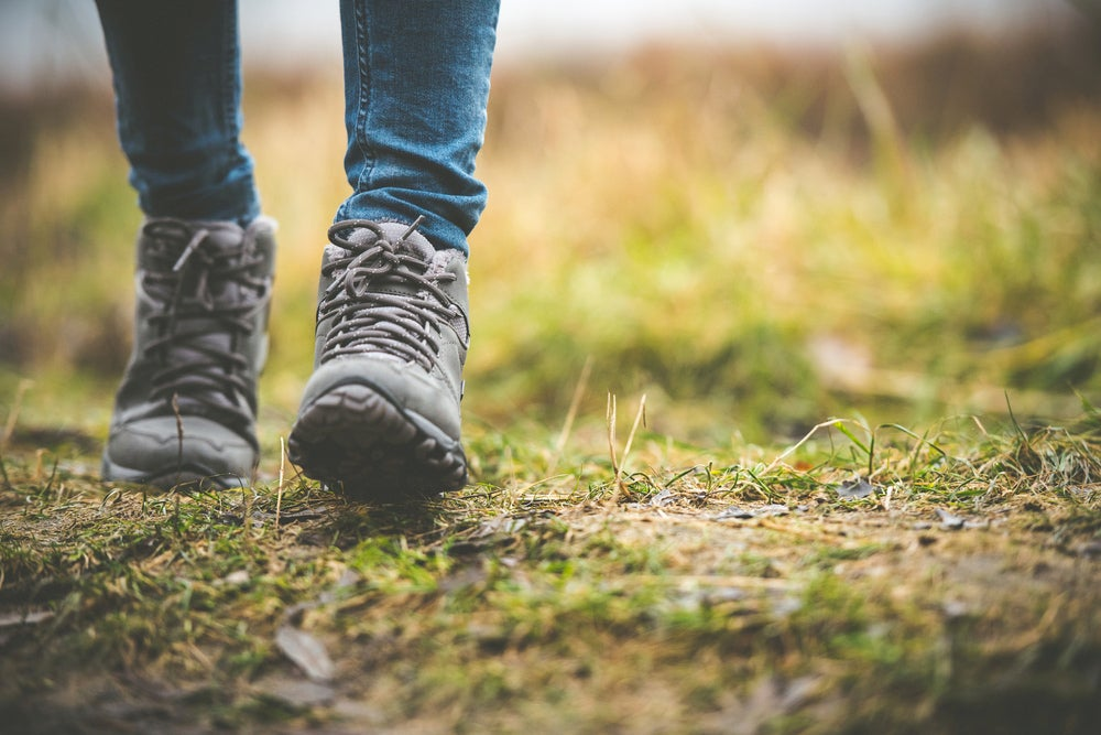Ground-level view of person in hiking boots walking along a grassy path