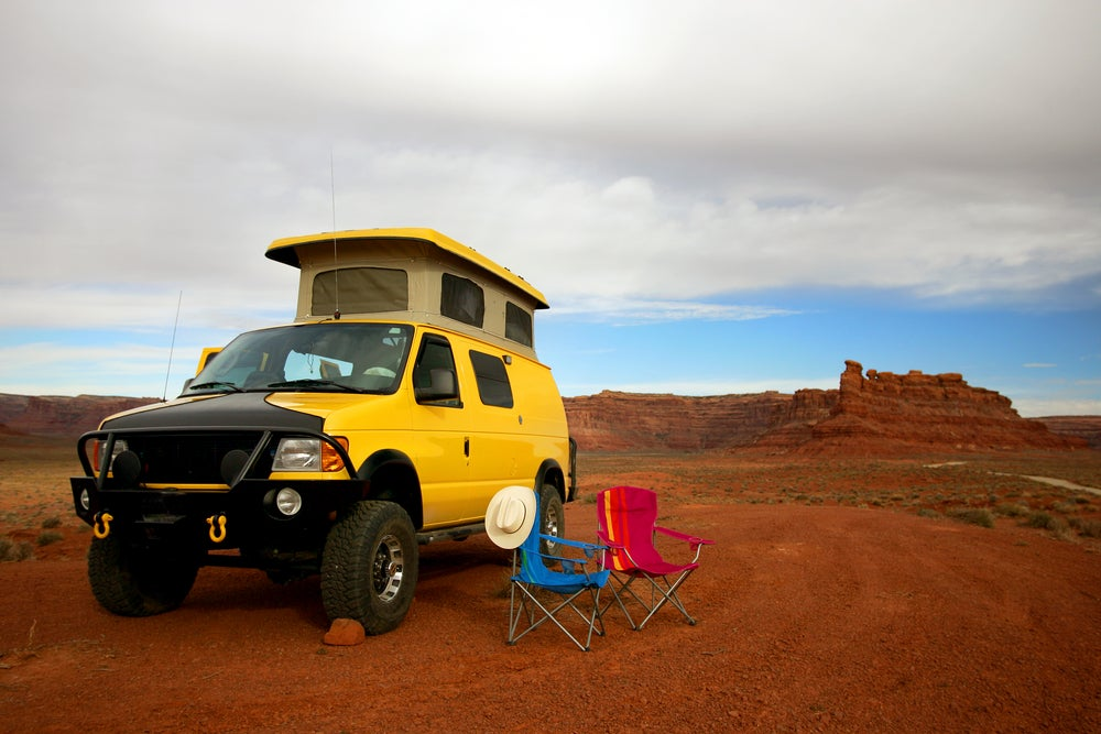 Yellow adventure van with a pop up top parked beside camp chairs in Utah desert.