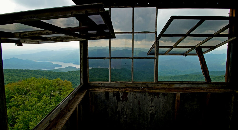 Large windows inside a fire tower tilted open to display green rolling hills and a river