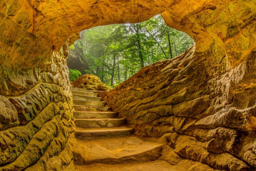 Yellow colored rock wall formation with natural staircase winding through an underground walkway.
