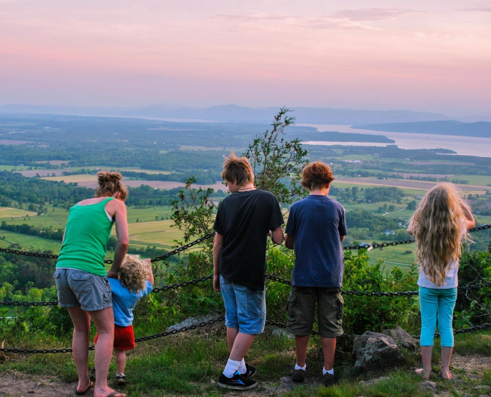 Mother and four children look over valley in Vermont at sunset