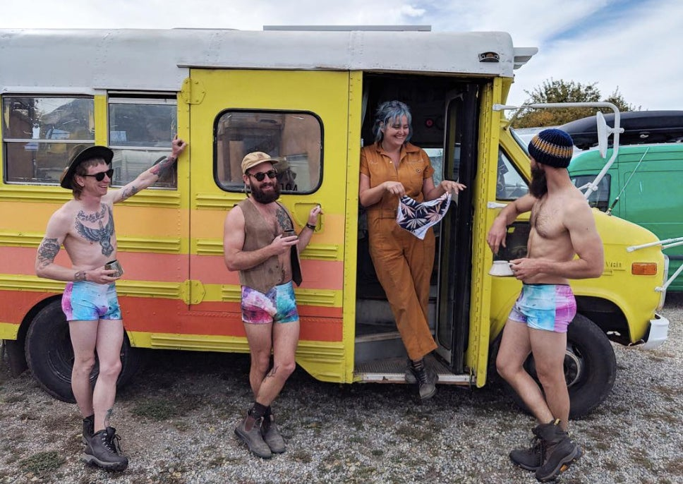 three men in bathing suits surround a woman in converted school bus as she holds a custom bathing suit