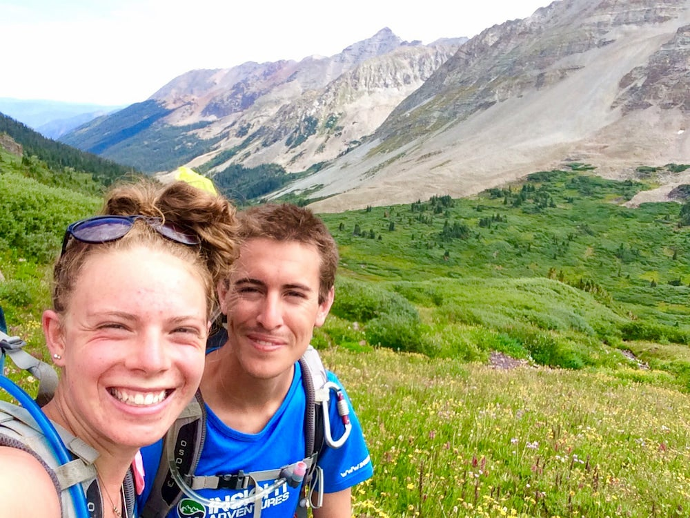 Two people hiking with wildflowers and mountains in background