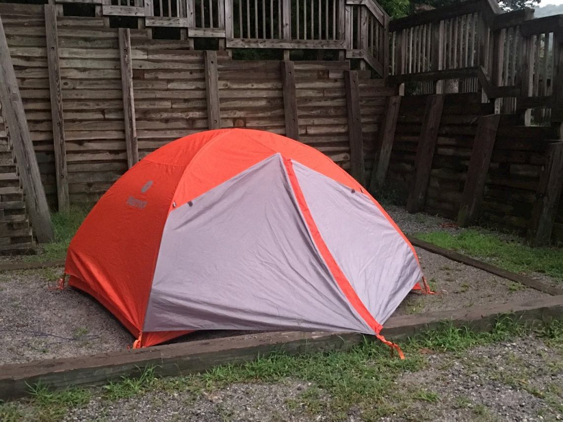 Orange tent setup in plot in front of wooden fence at Amicola Falls State Park.