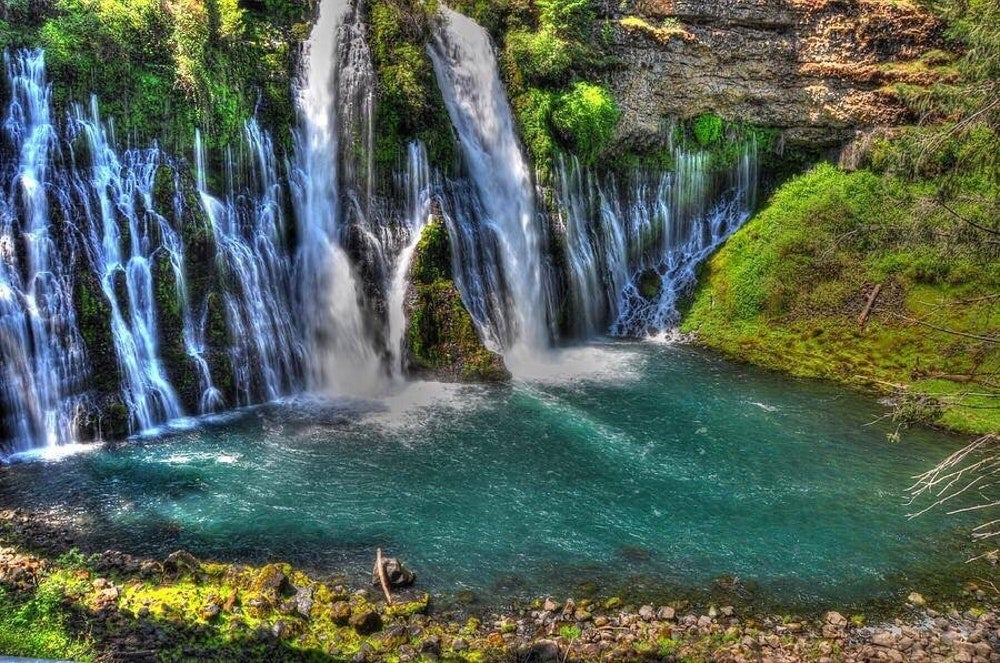 a number of waterfalls flowing from a rock cliff into a blue pool surrounded by moss