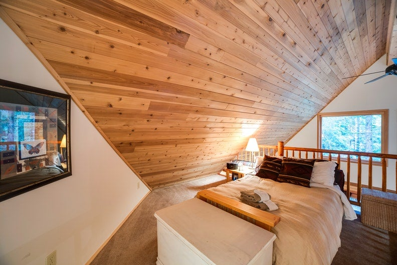 a lofted bedroom with a large TV and wooden walls in the mt. baker cabins