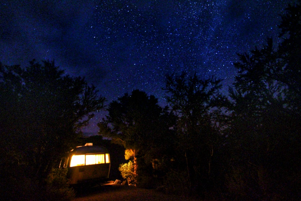 Airstream with light on and dark, starry sky in background