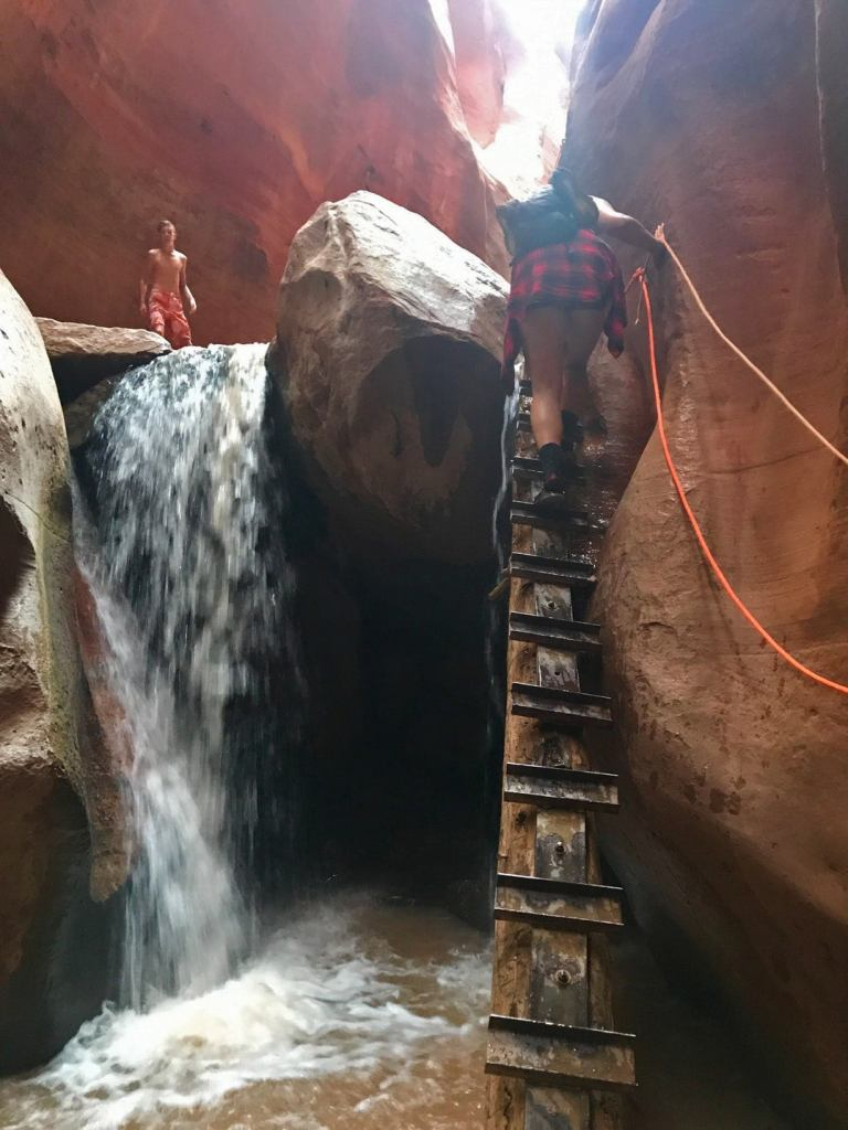 a woman climbing a wood ladder to reach the top of a small waterfall in a slot canyon in utah