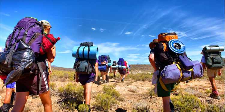 group of backpackers walking through sage brush