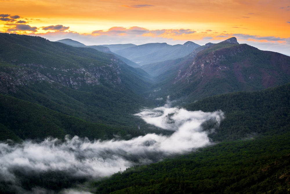 the linville river flows through the linville gorge at sunset