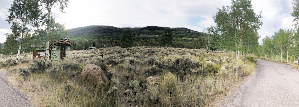Panorama of fields and surrounding hills at Mackinaw campsite.
