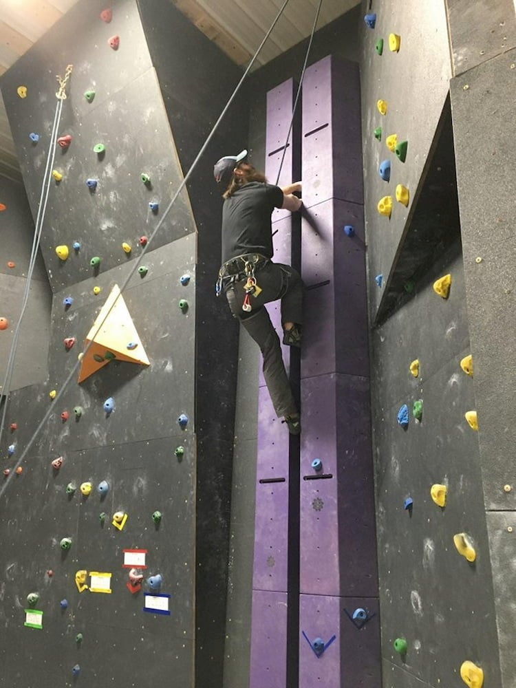 a man climbs a wall crack in a climbing gym