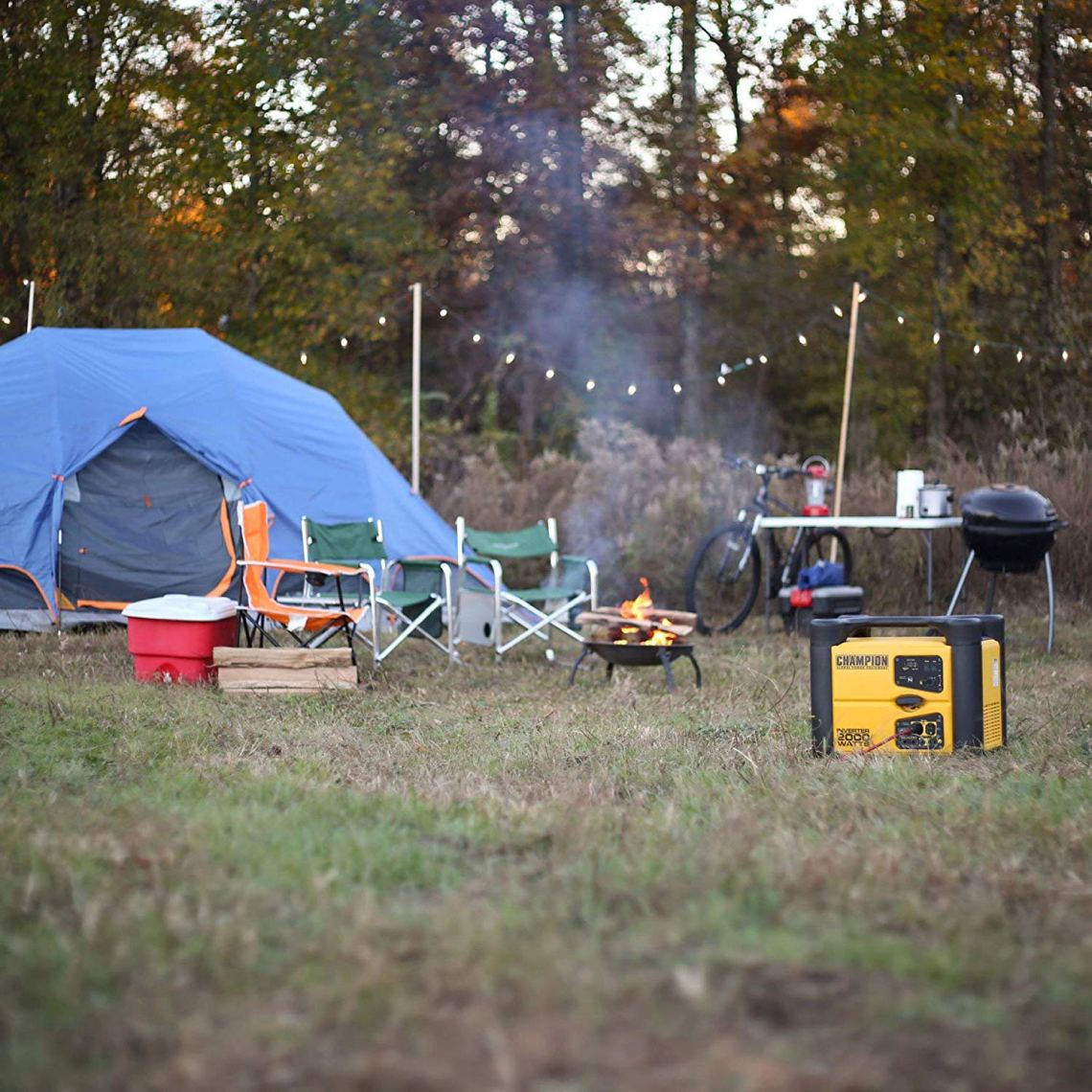 a camping generator set up at a campsite near chairs and tents plugged into lights
