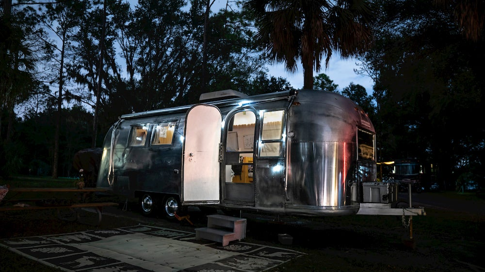 An open airstream RV parked at night in a campground