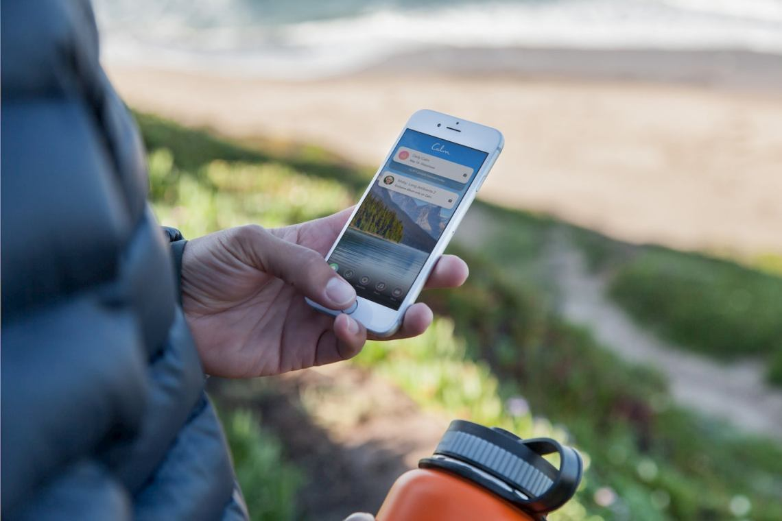 Person holding water bottle and smart phone, using the 'Calm' app