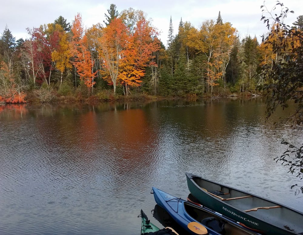 Canoes on a lake with fall trees in background