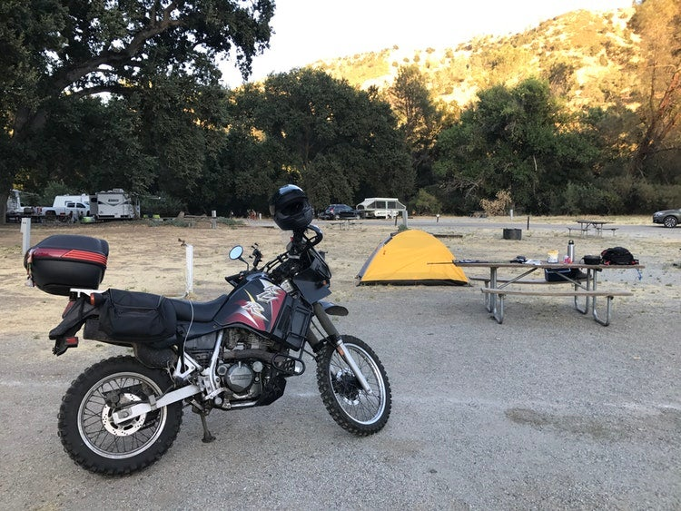 a motorcycle, tent and picnic table resting at a campground in california