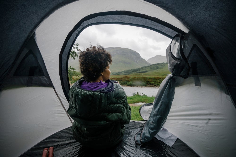 a woman sitting in a tent while it rains