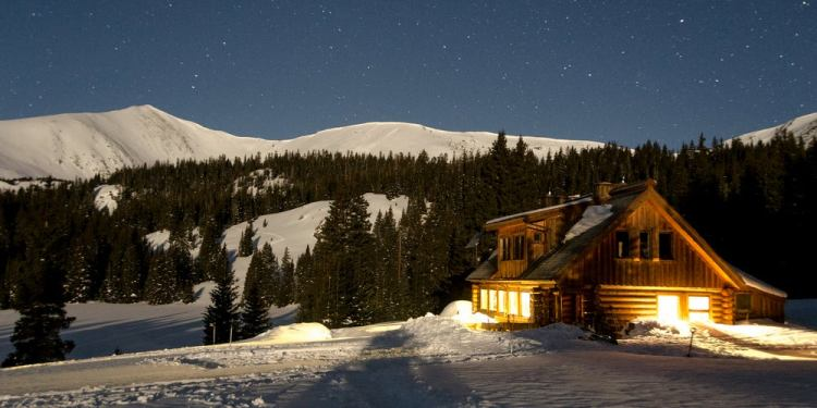 10th Mountain Division Hut lit up at night against snow covered mountains.
