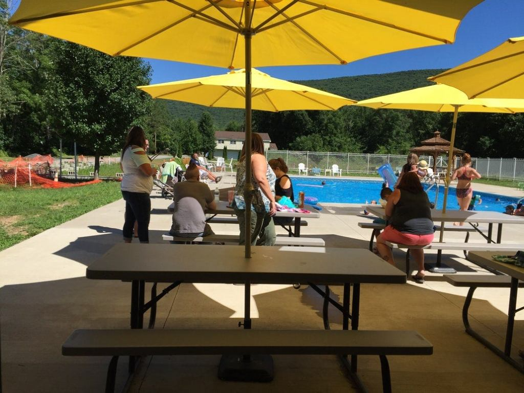 a family sits at picnic tables near a pool