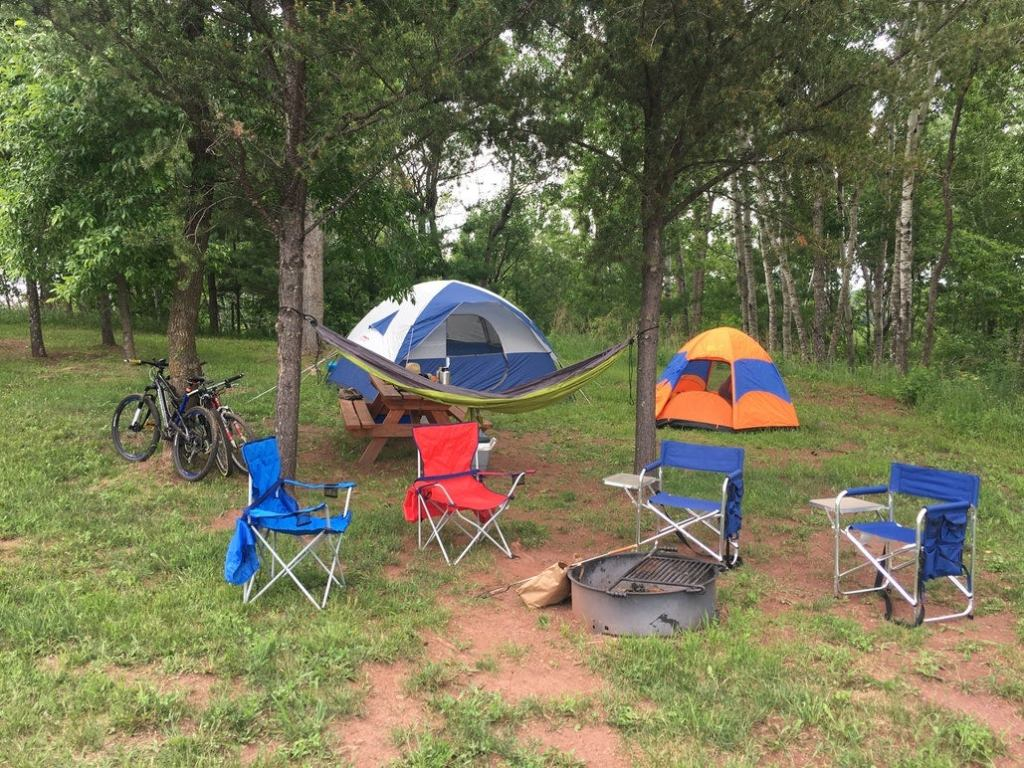 a campsite with two tents, four chairs and mountain bikes in minnesota