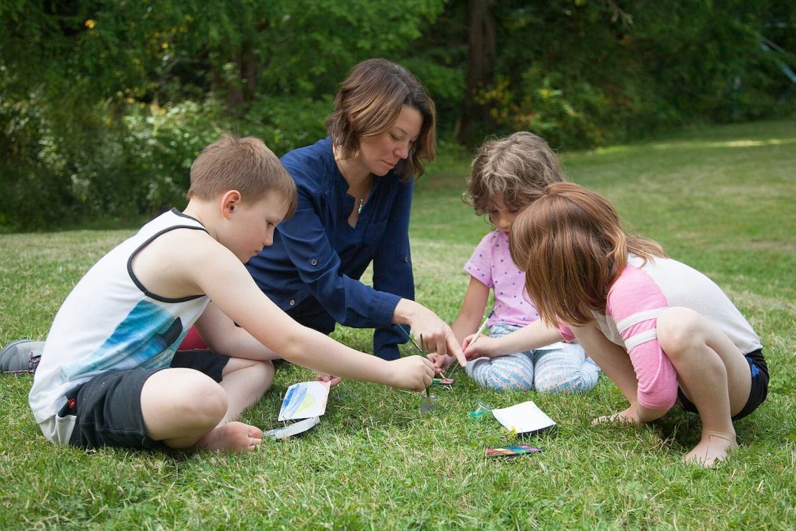 Teacher and students looking at notebooks on a grassy lawn.