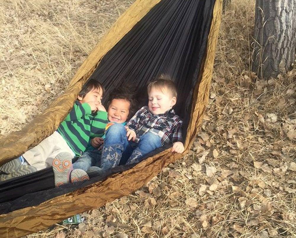 Three little boys giggling in a hammock.