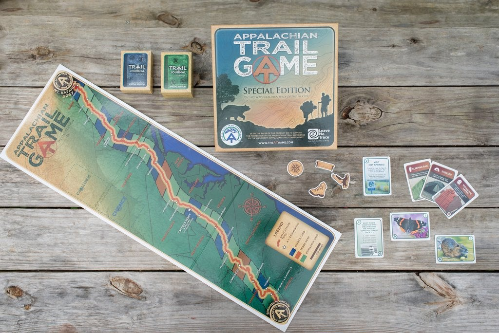 a wooden table set up with the Appalachian trail game cards and a map