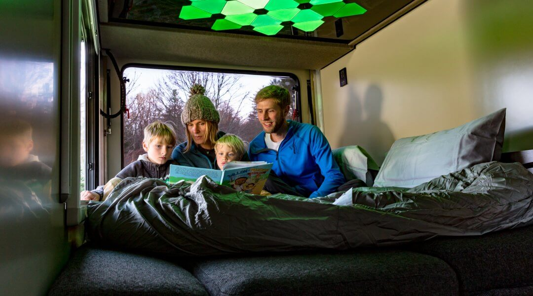 parents read a book to their two children beneath modern light panels in a camper