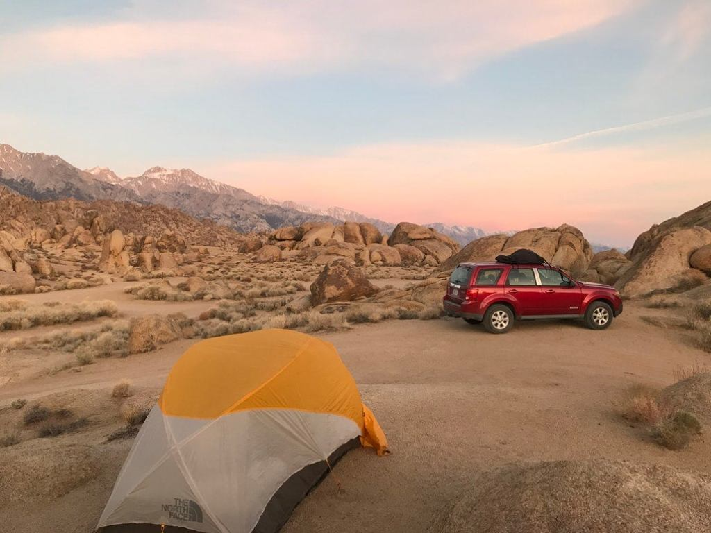 a red car and a tent set up between rocks in a desert in california