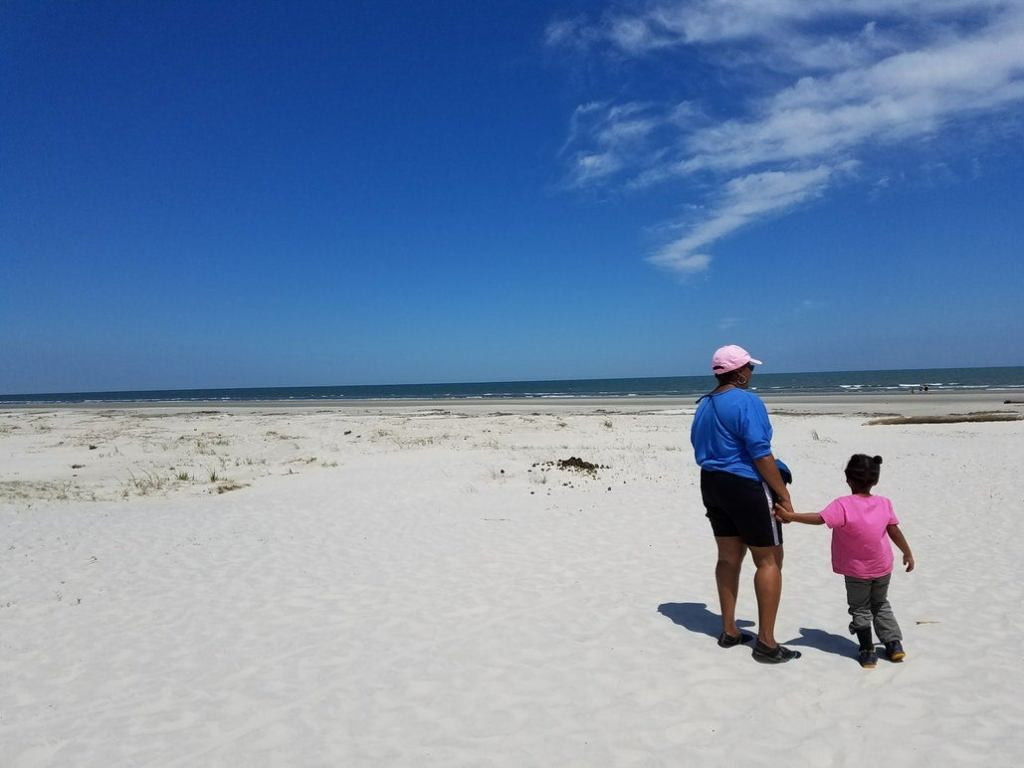 a mother and child on a white sand beach in georgia