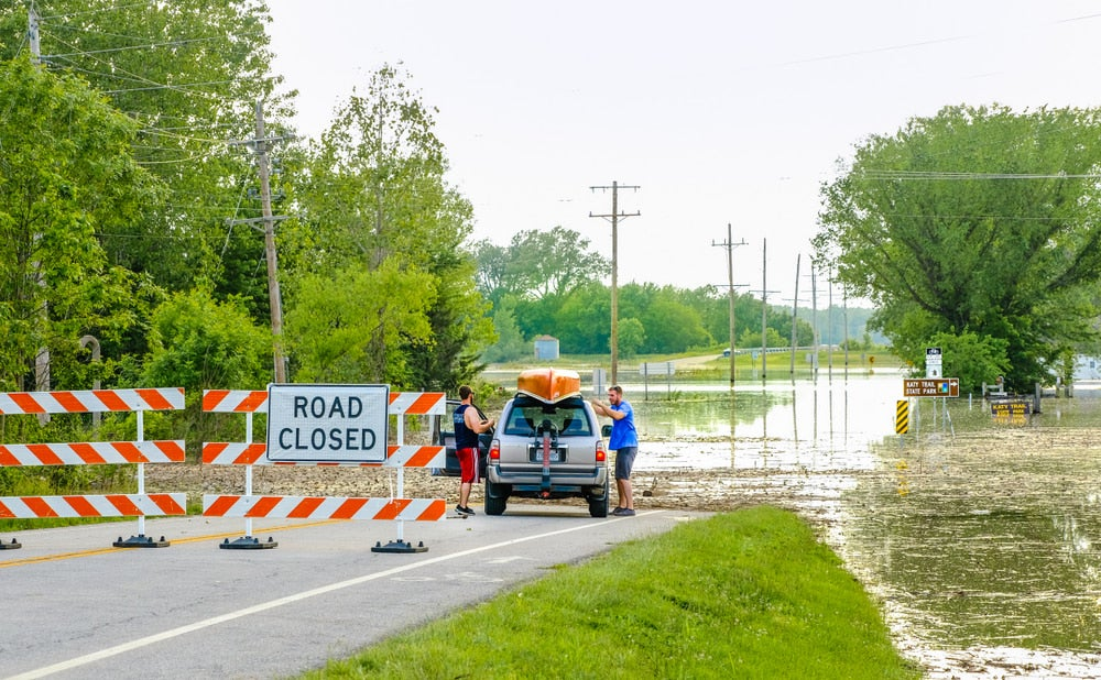 a car near a road block in missouri with a flood flowing over the road