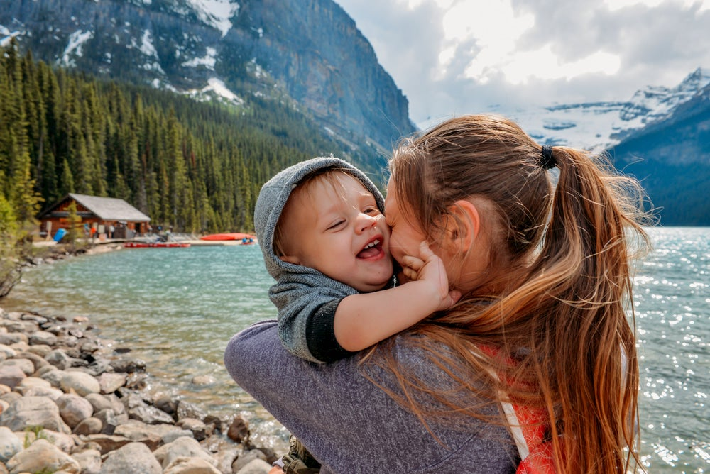 Baby and mother hugging with mountains in background