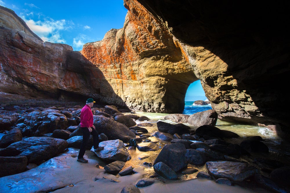 a person walking through the devils punch bowl on the oregon coast