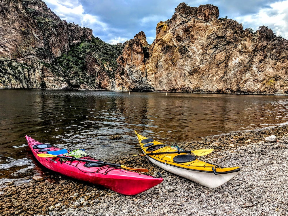 Two kayaks on shore with rock wall in background
