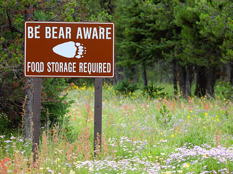 bear aware food storage sign on a trail