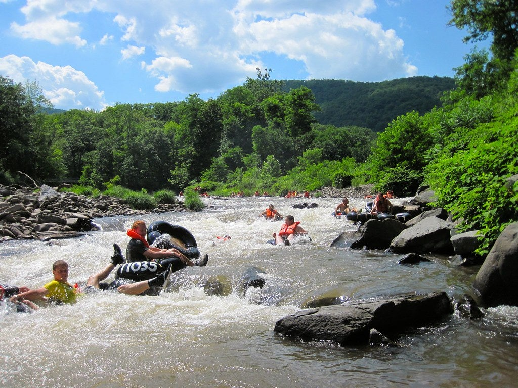 many people flying down river rapids in tubes in new york