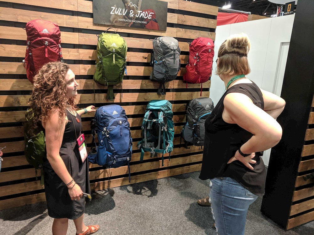two women looking at backpacks at outdoor retailer 2019
