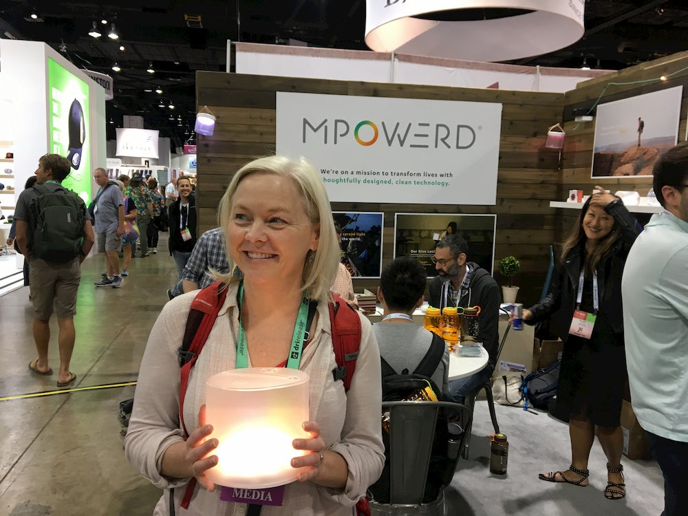 a woman holding a camping light on the show floor of outdoor retailer