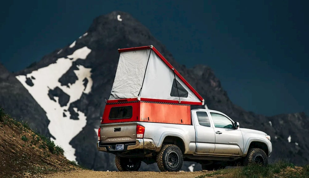 Truck with rooftop tent and mountains in background