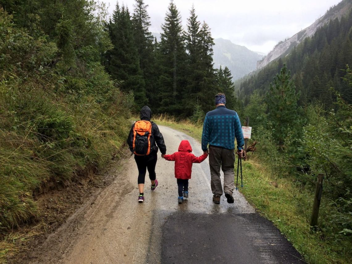 Parents holding infants hands while hiking.