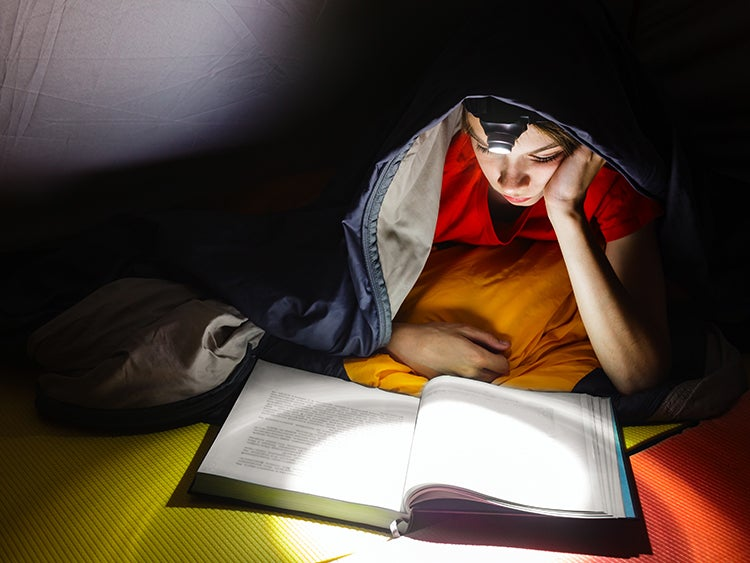 child reading in tent with headlamp