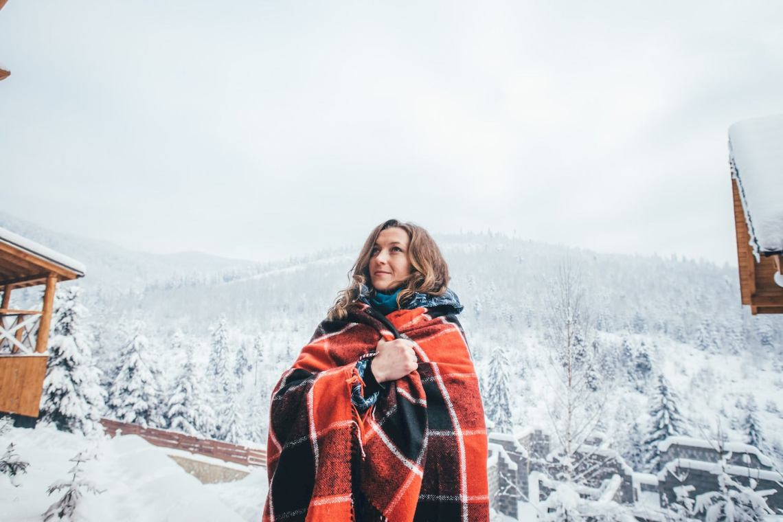 Women wrapped in a red flannel blanket in a snow covered landscape.