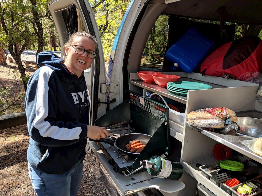 Woman cooking breakfast in van