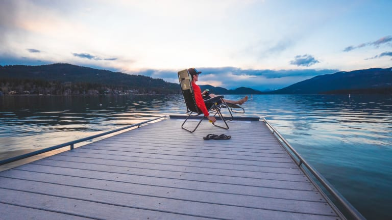 a man sitting in a chair on a dock at dusk