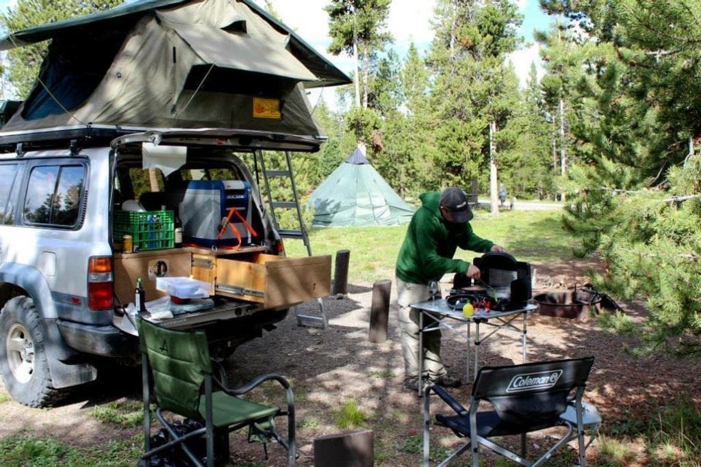 a man at a campground with a car, table and tent set up